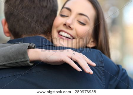 Happy Girlfriend Looks At Engagement Ring Hugging Her Boyfriend After Marriage Proposal