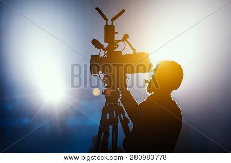 Cameraman Silhouette On A Live Studio News Stage.professional Cameraman With Headphones In Televisio