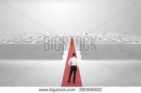 Businessman going straight ahead on a red carpet arrow between two maze
