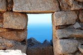 Looking through the window of the medieval Knights of Saint John crusader castle near Horio on the Greek island of Halki. poster