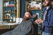 Hipster bearded client got hairstyle. Barber with hairdryer blows off hair out of cape. Barbershop concept. Barber with hairdryer works on hairstyle for bearded man, barbershop background poster