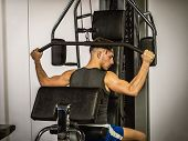 Muscular young man, training pecs on gym machine poster