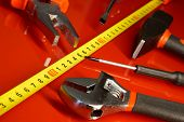 Tape measure, screwdriver, hammer, pliers and other tools lie on a red polished surface in a car repair shop. Devices for work of the mechanic and the joiner. Close-up poster