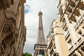 Paris, France 02 June 2018 small paris street with view on the famous paris eifel tower on a cloudy summer day with some sunshine. poster