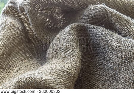 Burlap Texture Fabric In Folds Background Close Up