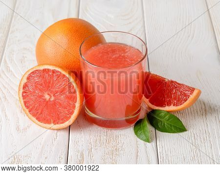 Glass Of Freshly Squeezed Grapefruit Juice With Pulp And Whole, Half And Quarter Grapefruits On A Wh