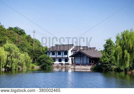 A Tree Lined Pond And Chinese Building Within The East Lake, Dong Hu, Scenic Area In Shaoxing China
