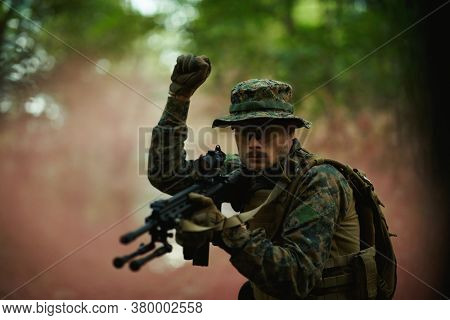 modern warfare soldier officer is  showing tactical hand signals to silently give orders and alers for squad team forest enviroment