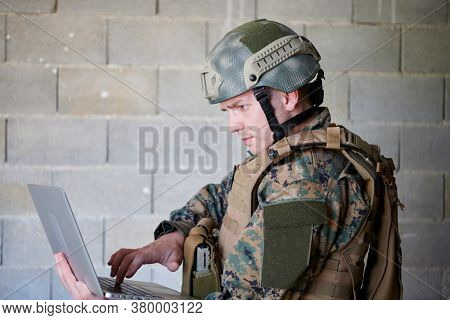 American soldier in military uniform using laptop computer for drone controlling and to stay in contact with friends and family