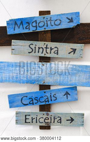 Wooden Direction Signboard With Arrows And The Names Of Sintra, Magoito, Cascais And Ericeira, Famou
