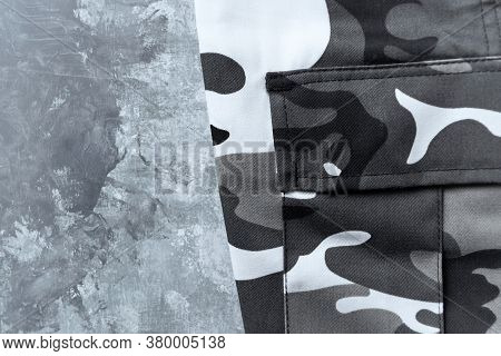 Trousers With A Camouflage Pattern On A Wooden Background. Top View. Copy Space.