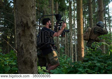 Videographer with Professional Movie Video Camera Gimbal Stabilizing Equipment Taking Action Shoot of Soldiers in Action in Forest