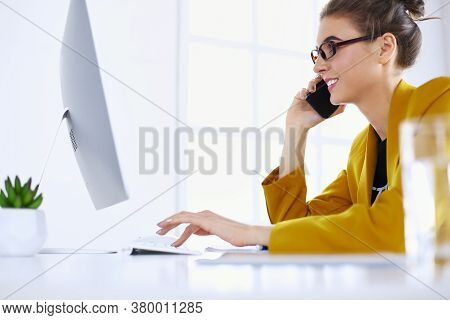 Businesswoman Concentrating On Work, Using Computer And Cellphone In Office