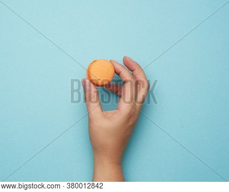 Female Hand Hold Round Baked Orange Macaron Cookie On A Blue Background, Place For An Inscription, T
