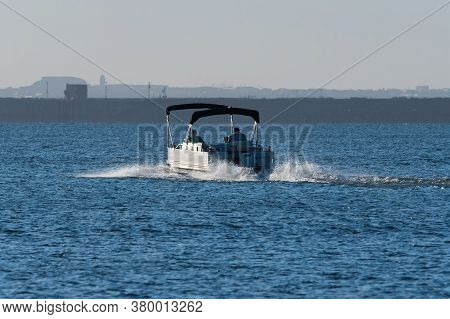 Pontoon Boat With Twin Canopies Heading Out For A Day On The Lake In The Warm Glow Of The Early Morn