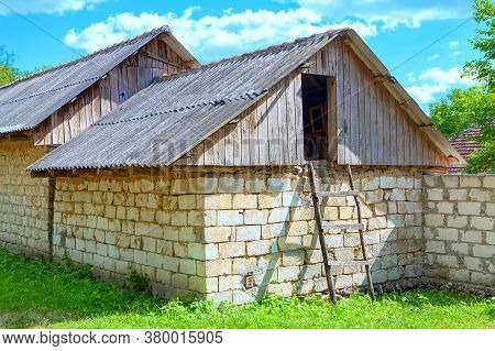 Barn In The Village . Exterior Rural Wooden Stairs To The Attic . Bricks Wall