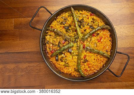 Vegetable Paella Rice With Vegetables In Paella Pan, On Wooden Background.