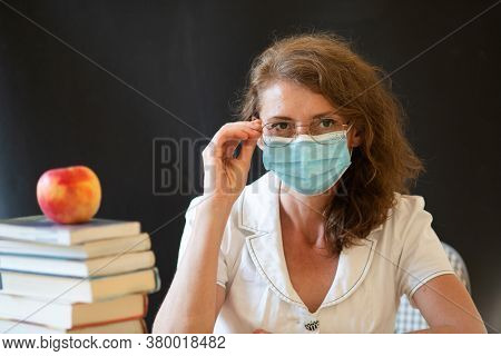 back to school during covid pandemics teacher with face mask