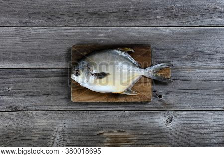 Overhead View Of A Fresh Whole Silver Or White Pomfret Fish On Wooden Serving Board