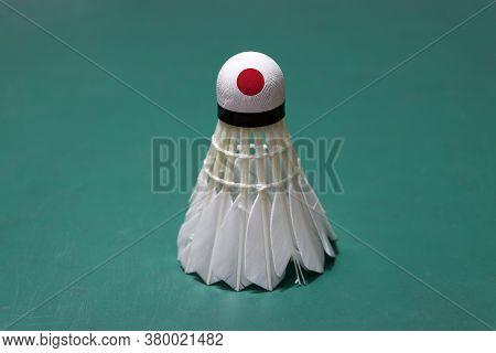 Used Shuttlecock And On Head Painted With Japan Flag Put Vertical On Green Floor Of Badminton Court.