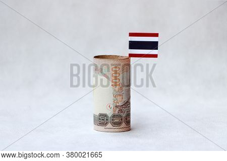 Rolled One Thousand Baht Banknote Of Thailand And Mini Thai Flag On The White Floor. Concept Of Curr