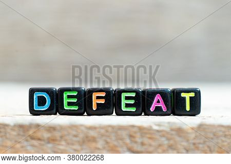 Black Bead With Color Letter In Word Defeat On Wood Background