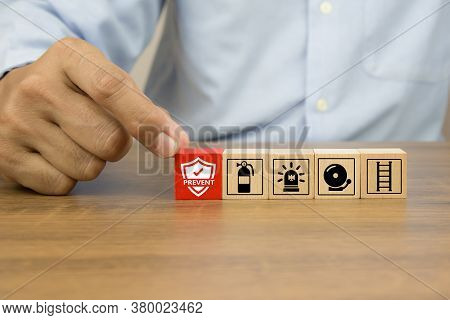 Close-up Hand Choose Prevent Icon On Cube Wooden Toy Blocks Stacked With Fire Exit Prevention Icon F