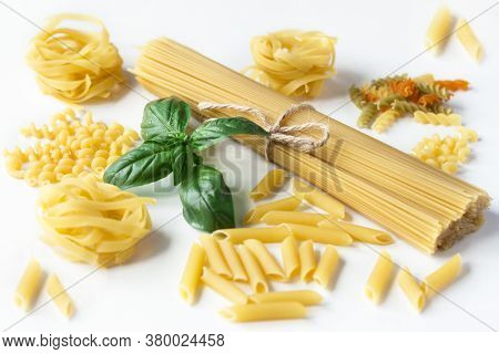 Raw Dry Pasta Is Lying On A White Table, Spaghetti Tied With Brown Twine, Tagliatelle, Colored Pasta