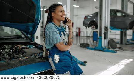 Young African American Woman, Professional Female Mechanic Talking On Phone, Leaning On A Car With O
