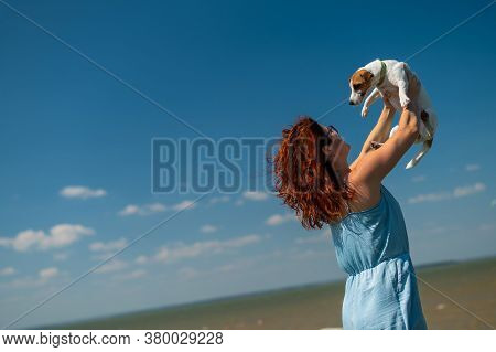 Happy Woman Hugs With A Dog By The Sea. Red-haired Caucasian Girl Holding A Jack Russell Terrier Pup
