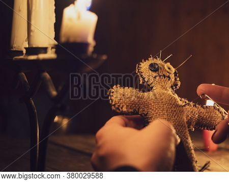 A Sorceress Pierces A Voodoo Doll With A Pin, Causing Harm Or Damage To A Person, Close-up. Magical,