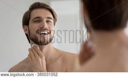 Close Up Mirror Reflection Overjoyed Young Man Applying Aftershave Lotion