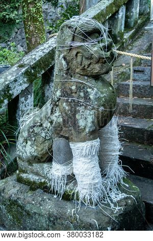 Stone Carved Statue Of A Guardian Dog In Suwa Shinto Shrine In Nagasaki, Japan. Dog Is Wrapped With