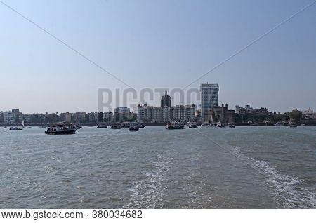 MUMBAI, INDIA - FEBRUARY 15, 2020: Taj Mahal hotel, Gateway of India and tourist boats in water of Arabian Sea  in Mumbai, India
