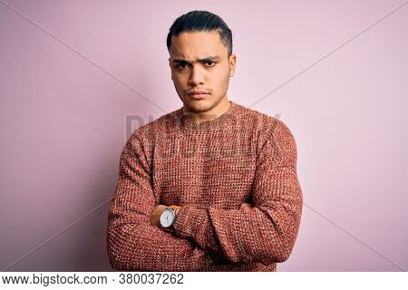 Young brazilian man wearing casual sweater standing over isolated pink background skeptic and nervous, disapproving expression on face with crossed arms. Negative person.