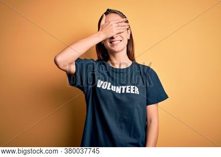 Young beautiful woman wearing volunteer t-shirt doing volunteering over yellow background smiling and laughing with hand on face covering eyes for surprise. Blind concept.