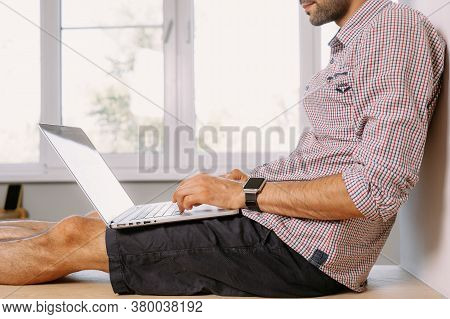 A Young Man In A Shirt Sits On The Windowsill And Works On A Laptop At Home