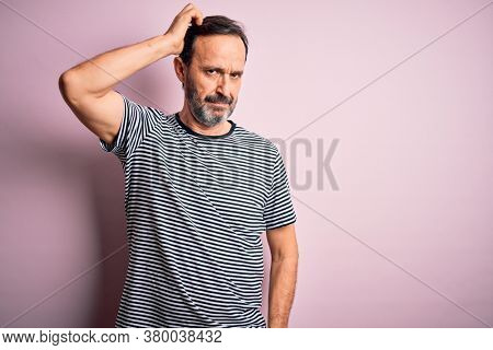 Middle age hoary man wearing casual striped t-shirt standing over isolated pink background confuse and wonder about question. Uncertain with doubt, thinking with hand on head. Pensive concept.