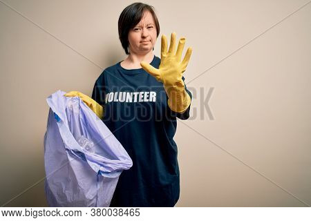 Young down syndrome volunteer woman picking rubbish and plastic from the trash with open hand doing stop sign with serious and confident expression, defense gesture
