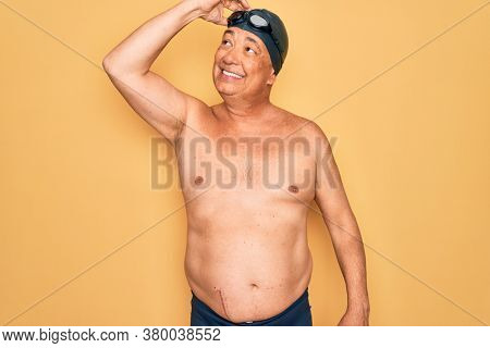 Middle age senior grey-haired swimmer man wearing swimsuit, cap and goggles smiling confident touching hair with hand up gesture, posing attractive and fashionable