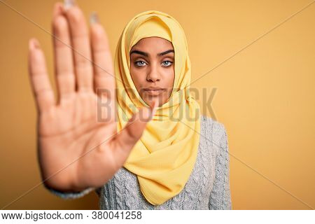 Young beautiful african american girl wearing muslim hijab over isolated yellow background doing stop sing with palm of the hand. Warning expression with negative and serious gesture on the face.