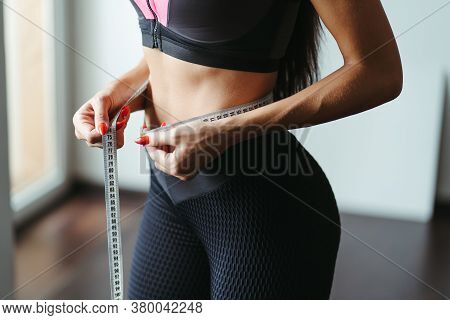 Fitness Motivation And Successful Weight Loss. Woman With Perfect Slim Body Measuring Her Waistline