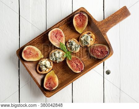 Toasts With Roquefort Cheese And Fresh Figs, On A Wooden Serving Board, On White Wood Background, To