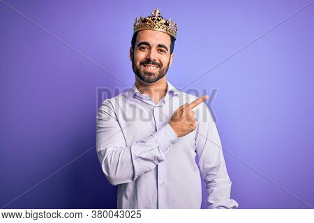 Young handsome man with beard wearing golden crown of king over purple background cheerful with a smile of face pointing with hand and finger up to the side with happy and natural expression on face