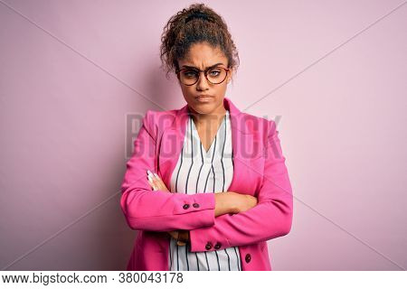 Beautiful african american businesswoman wearing jacket and glasses over pink background skeptic and nervous, disapproving expression on face with crossed arms. Negative person.