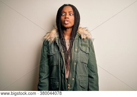 Young african american woman wearing winter parka coat over isolated background making fish face with lips, crazy and comical gesture. Funny expression.