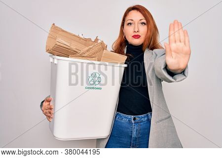 Young beautiful redhead woman recycling holding trash can with cardboard to recycle with open hand doing stop sign with serious and confident expression, defense gesture