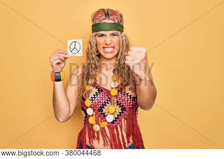 Blonde hippie woman wearing sunglasses and accessories holding reminder with peace symbol annoyed and frustrated shouting with anger, yelling crazy with anger and hand raised