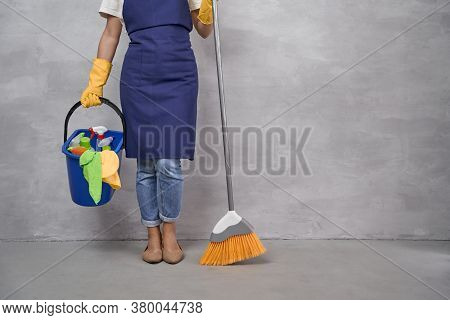 Professional Cleaning Service. Cropped Shot Of Woman In Uniform And Yellow Rubber Gloves Holding Bro