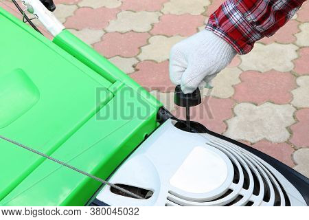 Male Checking The Oil Level In Lawn Mower. A Green Lawnmower. Gardening. Maintenance Of Equipment. M